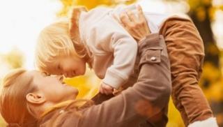 Mama i dziecko bawią się pośród liści