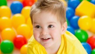 Chłopiec bawi się wśród kolorowych piłek
