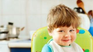 Uśmiechnięty chłopiec w śliniaczku siedzi w kuchni