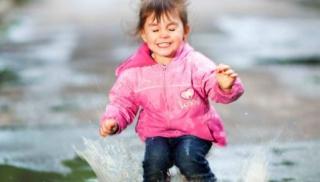 Dziewczynka na spacerze skacze po kałużach