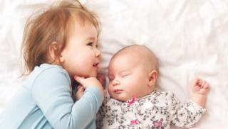Uśmiechnięte rodzeństwo leży na łóżku